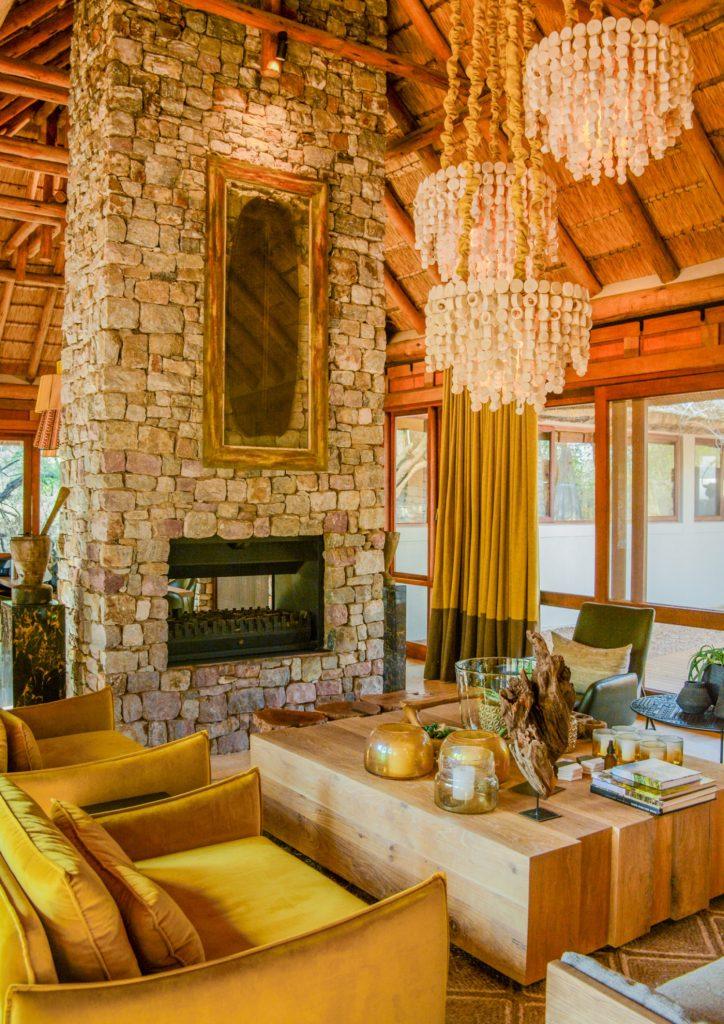 Madikwe, Living room, Indoor fireplace, Coffee table, Armchair, Hanging lights